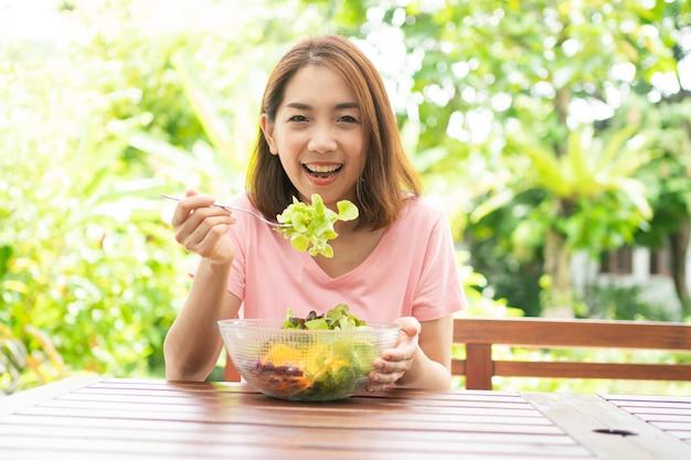 Mulher asiática bonita e saudável feliz sentada no terraço e comendo uma salada verde saudável