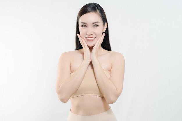 Mulher asiática bonita feliz que guarda seus mordentes com um riso que olha ao lado.