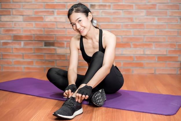 Mulher asiática bonita fitness é exercício em casa