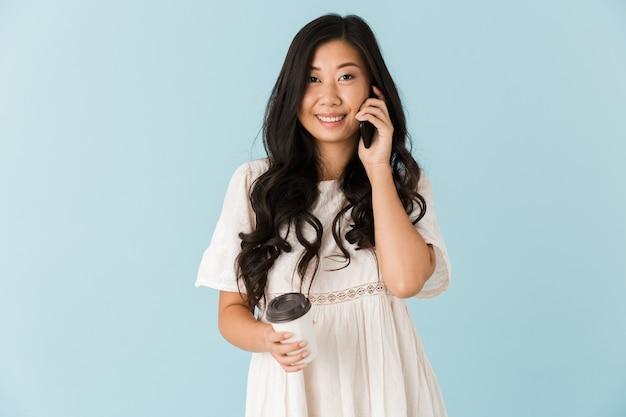 Mulher asiática bonita isolada sobre uma parede azul segurando café e falando por telefone