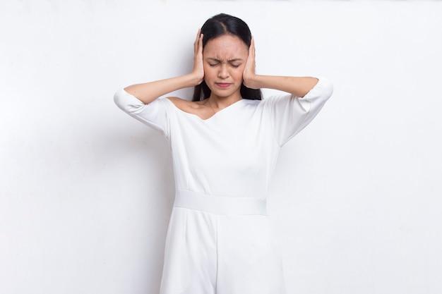 Mulher asiática bonita jovem cobrindo ambas as orelhas com as mãos isoladas no fundo branco