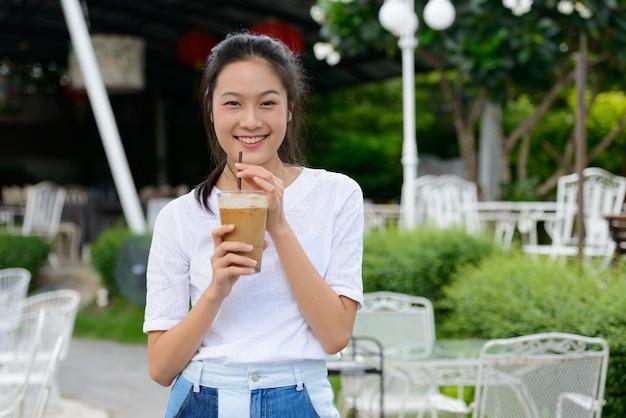 Mulher asiática bonita jovem feliz bebendo café em uma cafeteria ao ar livre