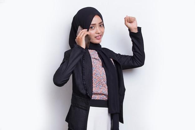 Mulher asiática bonita muçulmana jovem feliz usando telefone celular isolado no fundo branco