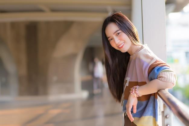 Mulher asiática bonita no suéter colorido em pé para descansar de uma caminhada no calor da cidade nos cuidados de saúde, poluição pm2.5 e novo conceito normal.