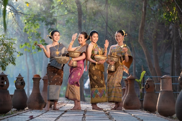 Mulher asiática bonita no tailandês que espirra tradicionalmente a água durante o festival da água songkran.