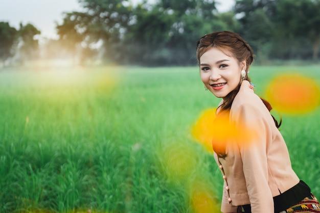 Mulher asiática bonita no vestido local sentado e desfrutar natural na ponte de bambu no campo de arroz