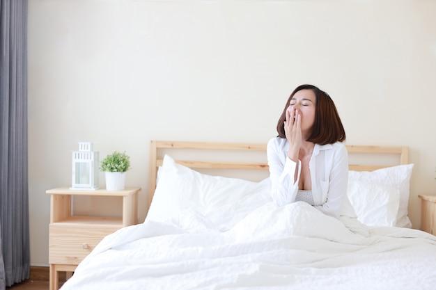 Mulher asiática bonita nova, cabelo curto que acorda na cama e que boceja na manhã no quarto