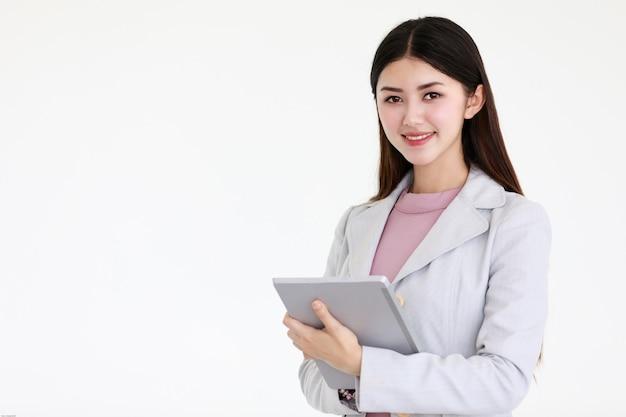 Mulher asiática bonita nova com cabelo preto longo que está na frente do fundo branco