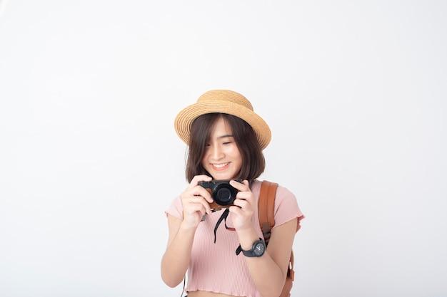 Mulher asiática bonita nova do turista feliz no estúdio branco da parede