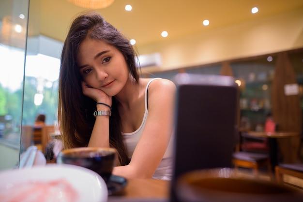 Mulher asiática bonita nova do turista que vlogging no restaurante com telefone móvel