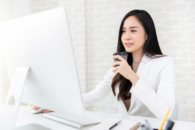 Mulher asiática bonita nova que bebe o café no trabalho