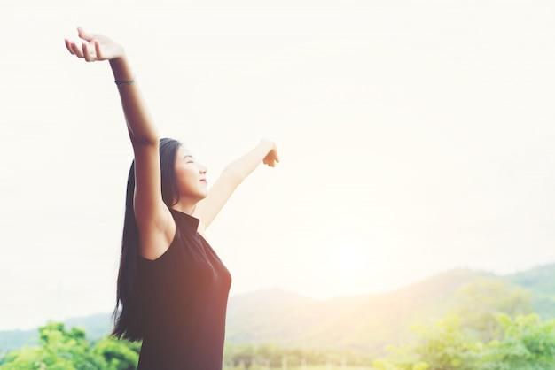 Mulher asiática bonita nova que está levantando as mãos para relaxar w Foto gratuita
