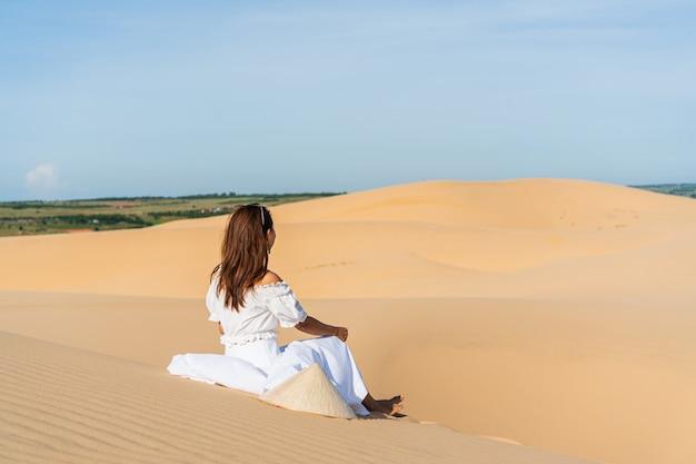 Mulher asiática bonita nova que levanta em um vestido branco no deserto branco da duna de areia, muine vietnam.