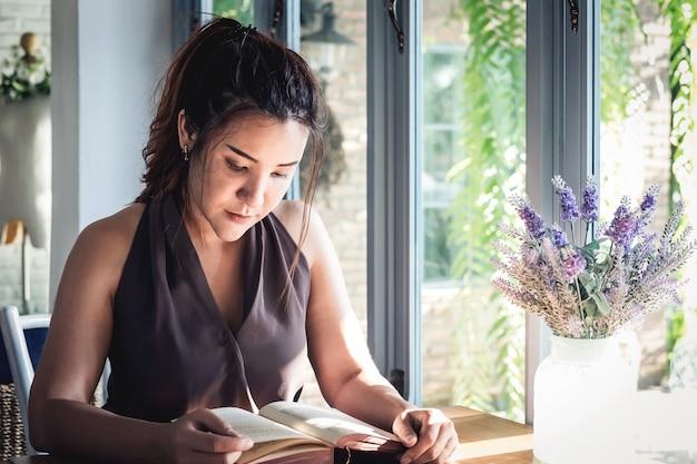 Mulher asiática bonita nova que senta-se na tabela e que lê livro interessante