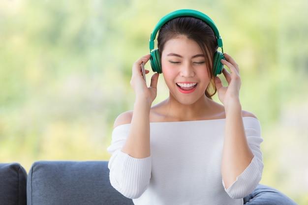 Mulher asiática bonita nova que senta-se no sofá e que escuta a música com o auscultadores no relaxamento.