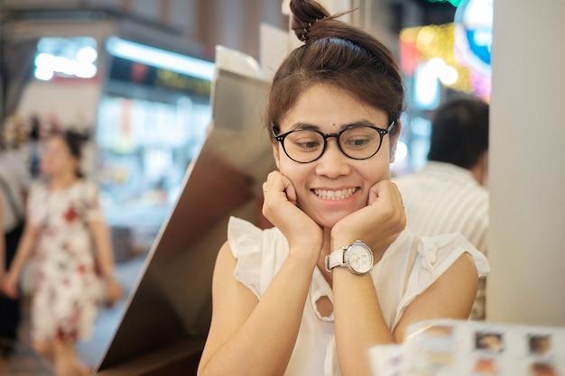 Mulher asiática bonita nova que sorri ao olhar o tempo de jantar do menu no restaurante ou na cafetaria