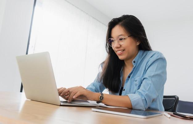 Mulher asiática bonita nova que trabalha com portátil, smartphone e tabuleta no escritório.