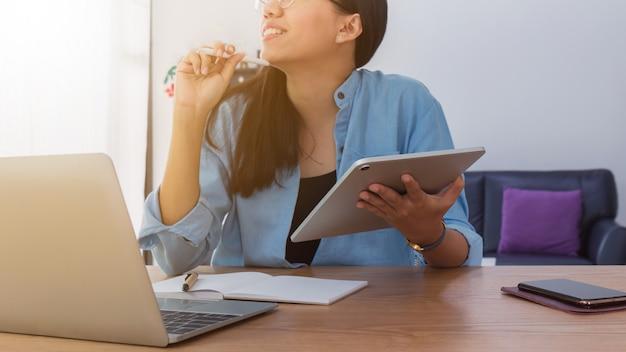 Mulher asiática bonita nova que trabalha com portátil, smartphone e tabuleta no fundo do escritório domiciliário