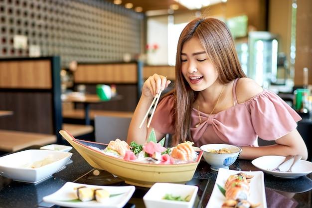 Mulher asiática bonita que come o sashimi, alimento japonês.