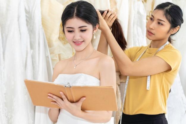 Mulher asiática bonita que escolhe o vestido em uma loja com assistente do alfaiate.