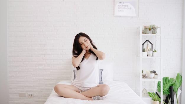 Mulher asiática bonita que estica seu corpo depois que acorda em seu quarto em casa.