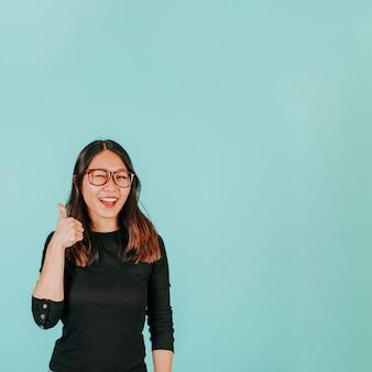 Mulher asiática bonita que gesticula polegar para cima