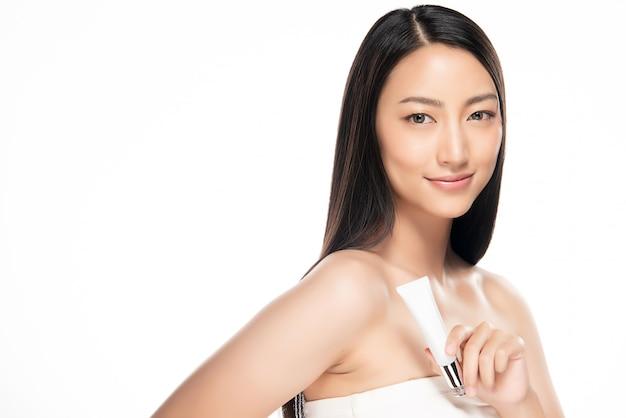 Mulher asiática bonita que guarda cosméticos no fundo branco.
