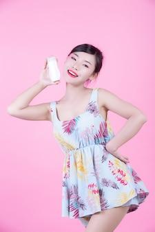 Mulher asiática bonita que guarda uma garrafa do produto em um fundo cor-de-rosa.