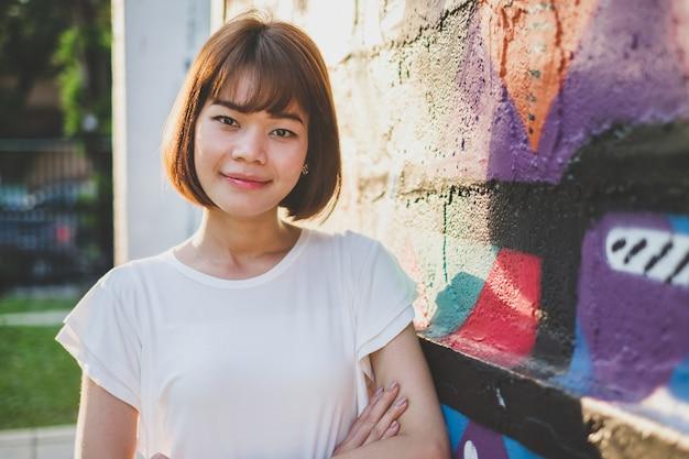 Mulher asiática bonita que olha a câmera ao estar em um fundo da parede da rua art graffiti