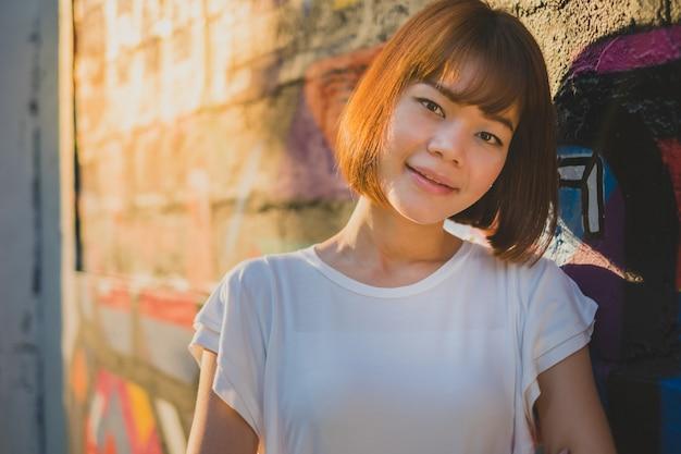Mulher asiática bonita que olha a câmera ao estar em uma parede da rua art graffiti