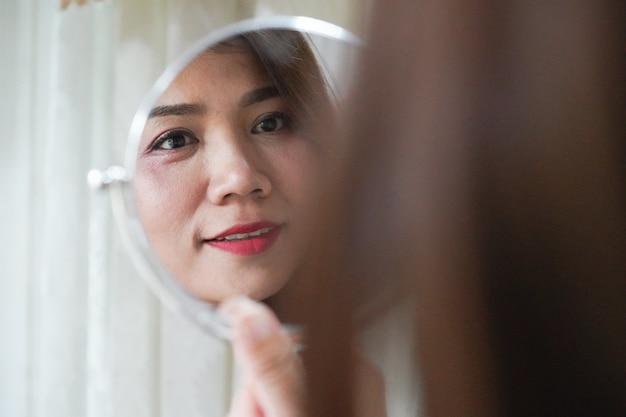 Mulher asiática bonita que olha o espelho para verificar suas rugas