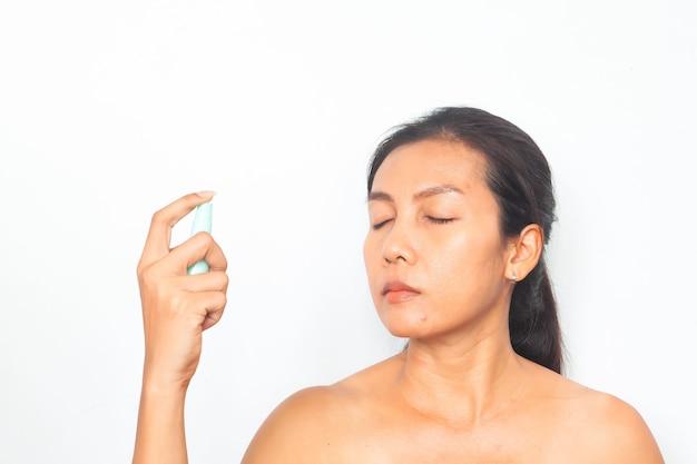Mulher asiática bonita que pulveriza a água mineral em sua face. conceito de beleza e saúde