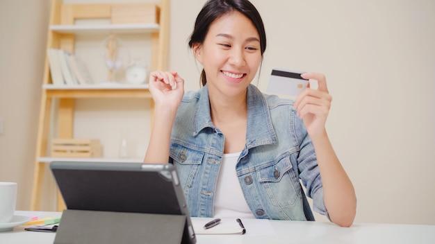 Mulher asiática bonita que usa a tabuleta que compra a compra em linha pelo cartão de crédito quando vestir o assento ocasional na mesa na sala de visitas em casa.