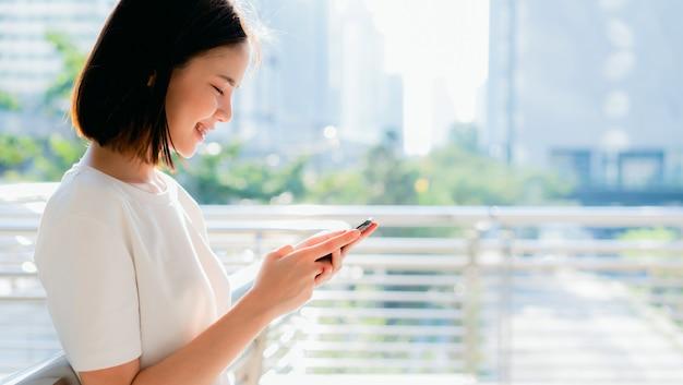 Mulher asiática bonita que usa o smartphone e estando no prédio de escritórios.