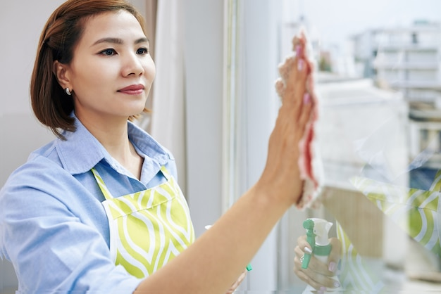 Mulher asiática bonita sorridente no avental limpando a janela do apartamento dela