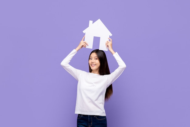 Mulher asiática bonita sorridente segurando sobrecarga de símbolo de casa isolada na parede roxa