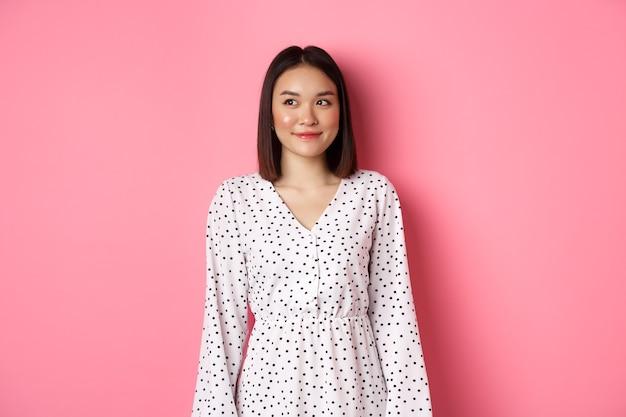 Mulher asiática bonita sorrindo, olhando para a esquerda no espaço da cópia, em um fundo rosa romântico
