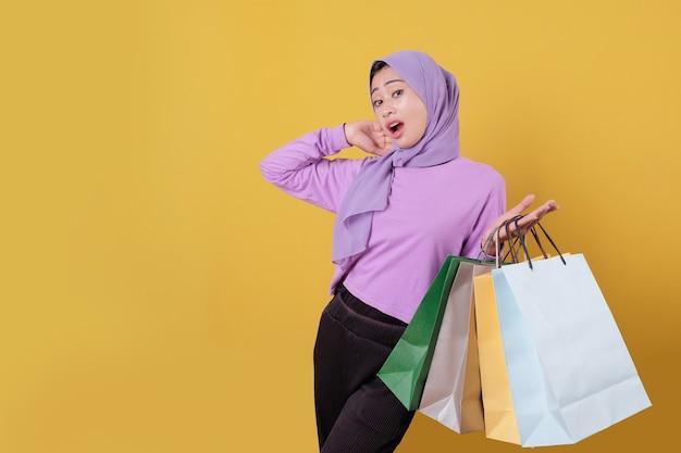 Mulher asiática bonita surpresa mostrando sacolas de compras, vestindo camiseta roxa