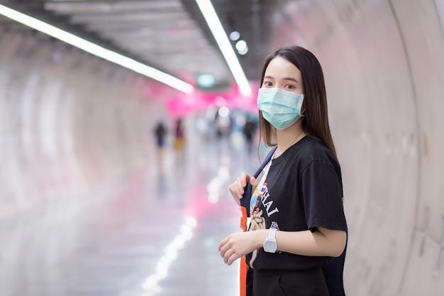 Mulher asiática bonita usa camisa preta e máscara facial médica enquanto caminha na estação de metrô