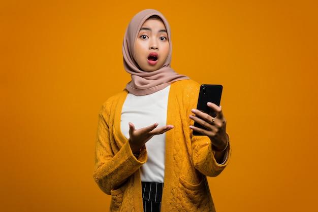 Mulher asiática bonita usando um smartphone com uma cara chocada
