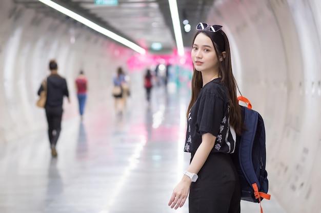 Mulher asiática bonita usando uma camisa preta, ela entra no túnel do metrô e segura uma mochila