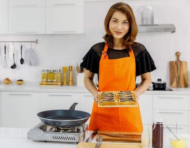 Mulher asiática bonita vestindo avental laranja cercando por aparelho de cozinha sorri e dá mostra a bandeja de pão saboroso coberto por creme de chocolate escuro.