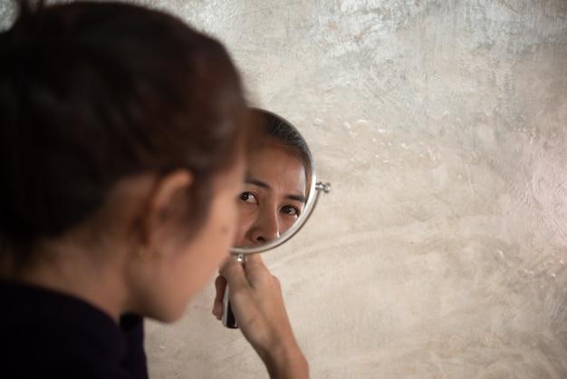 Mulher asiática brilha no espelho para ver rugas e cabelos grisalhos.