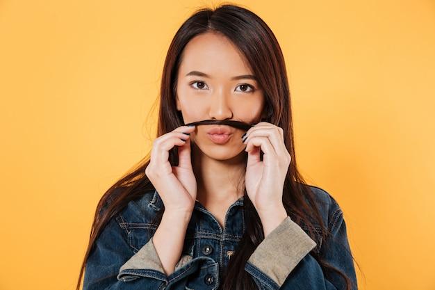 Mulher asiática brincalhão na jaqueta jeans, fazendo bigode falso