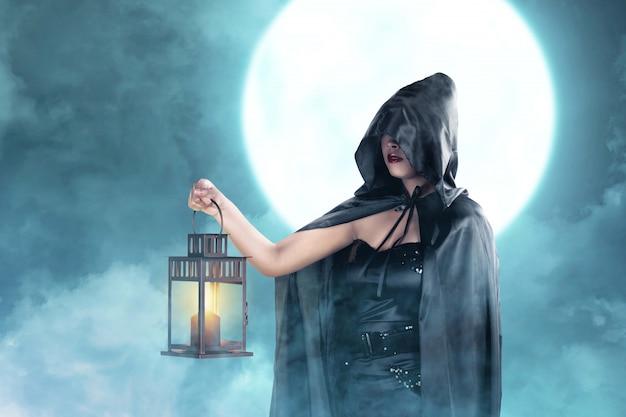 Mulher asiática bruxa com capa preta segurando lanterna em pé