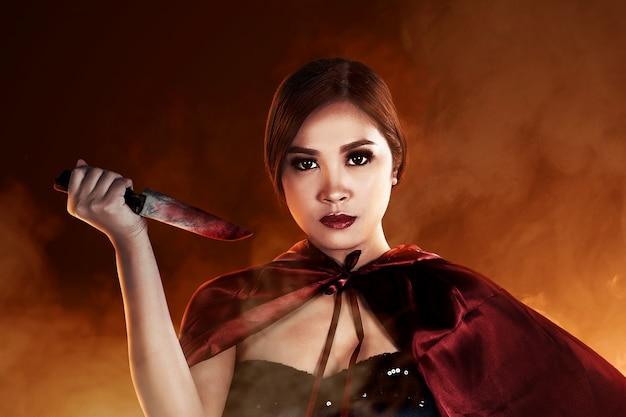 Mulher asiática bruxa segurando uma faca ensanguentada em pé