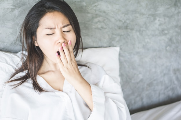 Mulher asiática cansada bocejando na cama
