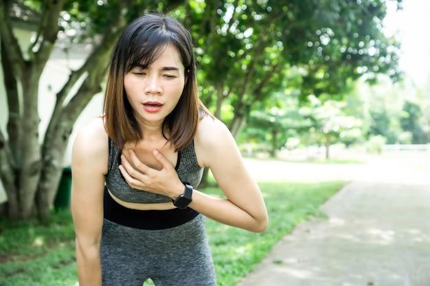 Mulher asiática cansada, sofrendo de ataque cardíaco enquanto praticava esportes, corria