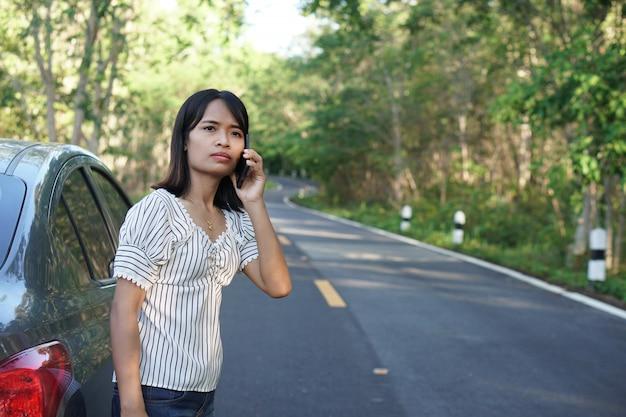 Mulher asiática chame um mecânico, o carro sai pela estrada ao redor da floresta.