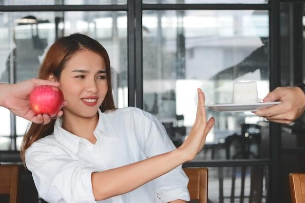 Mulher asiática chateada escolhendo entre apple ou bolo insalubre
